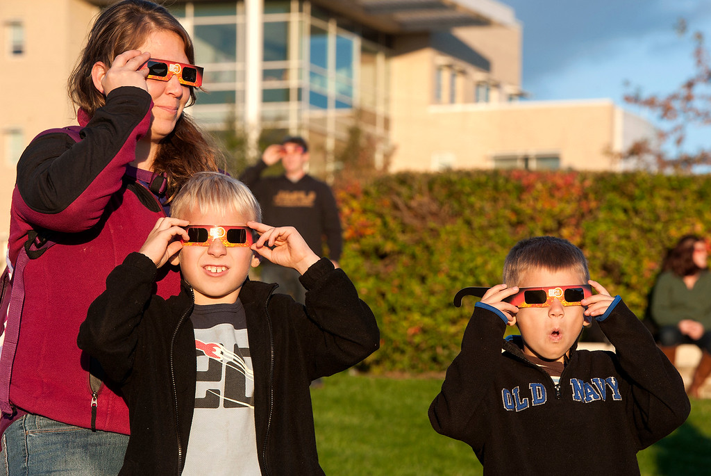 . Christine Toulson, of Singers Glen, watches over her two sons Nathan, center, 8, and Aidan, right, 6, as they watch Thursday\'s partial solar eclipse through special glasses at JMU\'s \'Astronomy Park\' in Harrisonburg, Va. The partial eclipse lasted several hours, but was only visible for about 30 minutes before the sun set. (AP Photo/The Daily News-Record, Jason Lenhart)