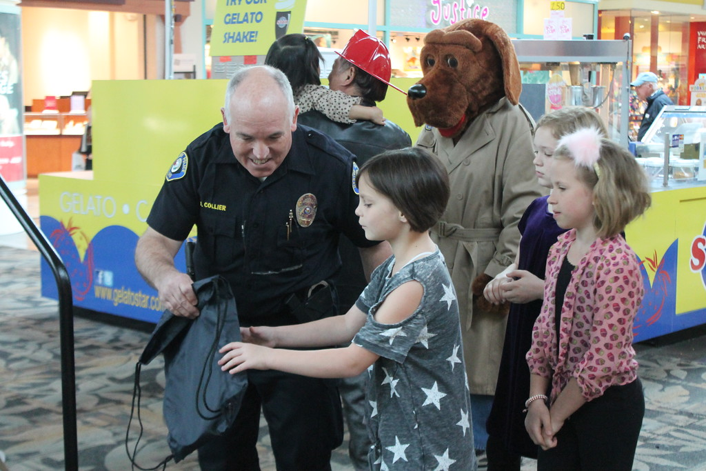. Kristi Garabrandt � The News-Herald <br> Mentor Community Policing Officer James Collier hands Eden Musser a bag with her awards for her overall third place finish in the third grade seat  belt safety poster contest held by Mentor Police Department each year. Eden received her prize during the 36th Annual Heroes Day held at Great Lakes Mall, May 12, 2018.