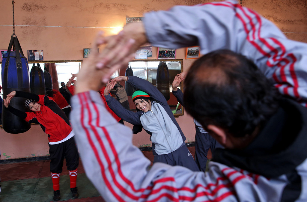 . In this Wednesday, March, 5, 2014 photo, Afghan women boxers warm up for practice at the Kabul stadium boxing club. The women, who are 18 and older, donít have much more than determination, and a trainer who runs them through their paces, watches as they spar, corrects their technique, tells them when to jab, how to protect themselves, when to power through with a left and then a right. (AP Photo/Massoud Hossaini)