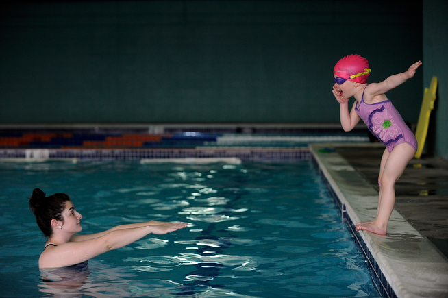 . Miranda Burke, 3, tells her swim instructor Rachel Trehey, 20, something as she stalls so she doesn\'t have to jump in the water at the Blue Dolphin Swim Training Center in Westminster, Colorado on April 23, 2014. Stacy Young is a swim coach who has taught in various pools around Adams County for the last 13 years. She recently opened the 8,000 square-foot Blue Dolphin Swim Center where she will continue to teach technical and competitive swimming to approximately 2,000 students every month. (Photo by Seth McConnell/The Denver Post)