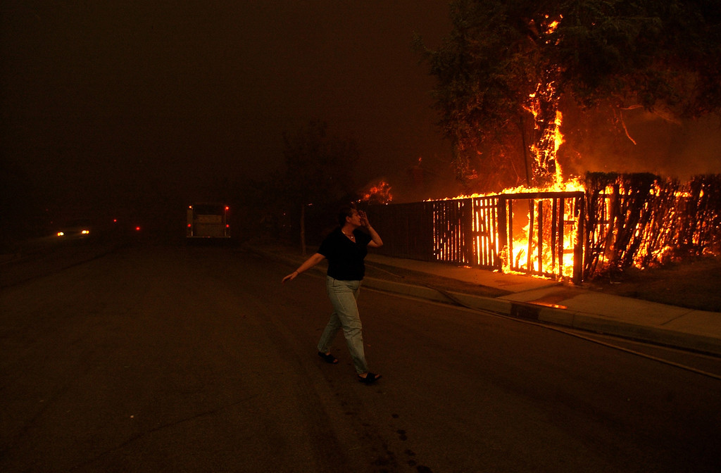 . Ten years ago this month the arson caused Old Fire, fanned by Santa Ana winds burned thousands of acres, destroyed hundreds of homes and caused six deaths. The fire burned homes in San Bernardino, Highland, Cedar Glen, Crestline, Running Springs and Lake Arrowhead and forced the evacuation of thousand of residents. An unidentified woman runs along Sonora Road at Golden Avenue as she waits for firefighters to save her property in north San Bernardino. (Staff file photo/The Sun)