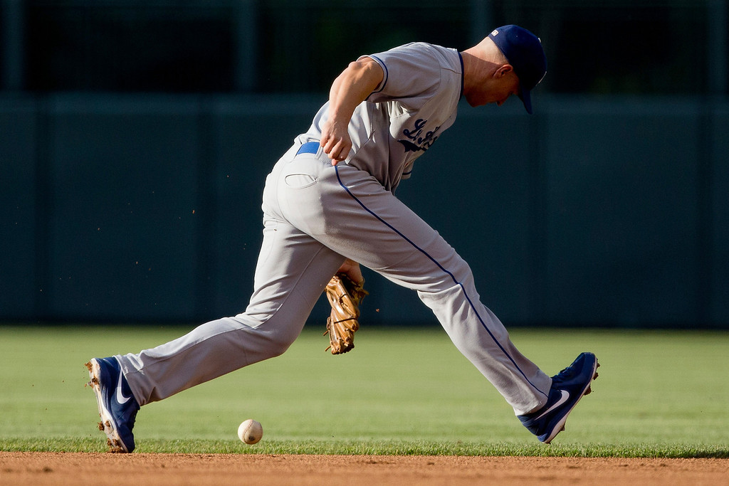. Second baseman Mark Ellis #14 of the Los Angeles Dodgers bobbles a ground ball during the first inning against the Colorado Rockies at Coors Field on July 2, 2013 in Denver, Colorado.  (Photo by Justin Edmonds/Getty Images)
