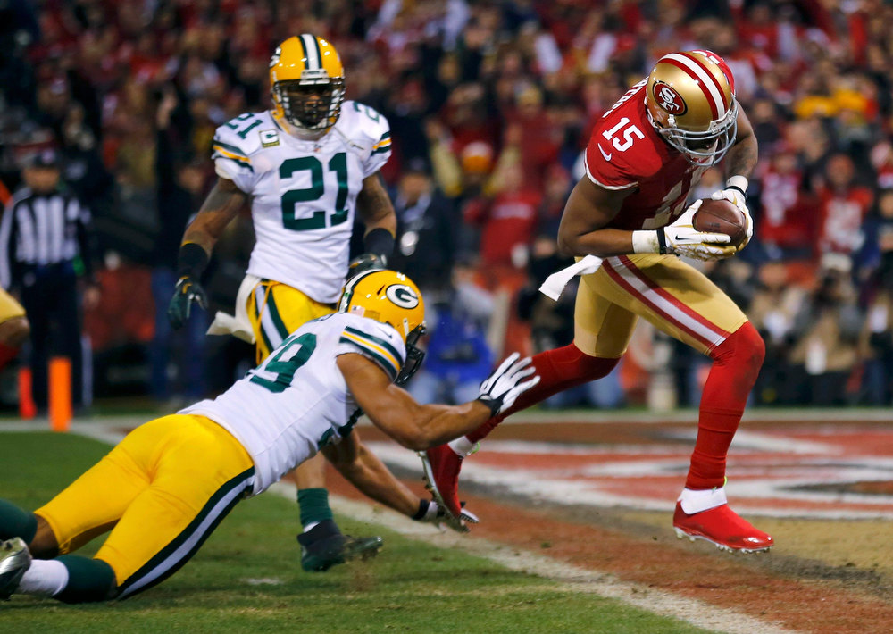 Description of . San Francisco 49ers Michael Crabtree (R) scores a touchdown past Green Bay Packers Charles Woodson (L)  and Brad Jones (C) in the second quarter during their NFL NFC Divisional playoff football game in San Francisco, California January 12, 2013.  REUTERS/Mike Blake