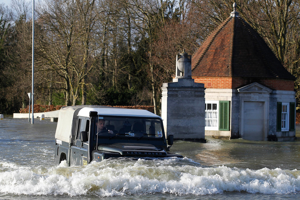 . A car drives through flood water, along a road at Runnymede, England, Thursday, Feb. 13, 2014.  The River Thames has burst its banks after reaching its highest level in years, flooding riverside towns upstream of London, with Runnymede being about 20 miles (32 Km) east of central London.(AP Photo/Sang Tan)