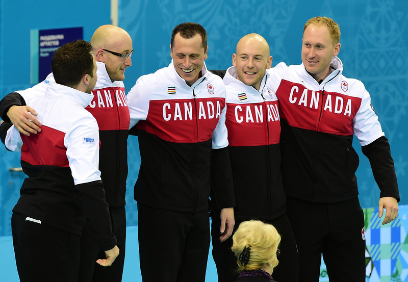 . Canada\'s gold medallists (L-R) Caleb Flaxey, Ryan Harnden, E.J. Harnden, Ryan Fry and Brad Jacobs celebrate on the podium during the Men\'s Curling Flower Ceremony at the Ice Cube Curling Center in Sochi during the Sochi Winter Olympics on February 21, 2014. JOHN MACDOUGALL/AFP/Getty Images