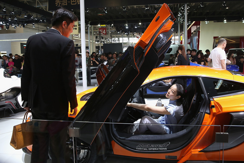 . A potential consumer sits in a McLaren sport car during the 2014 Beijing International Automotive Exhibition at China International Exhibition Center on April 21, 2014 in Beijing, China. (Photo by Feng Li/Getty Images)