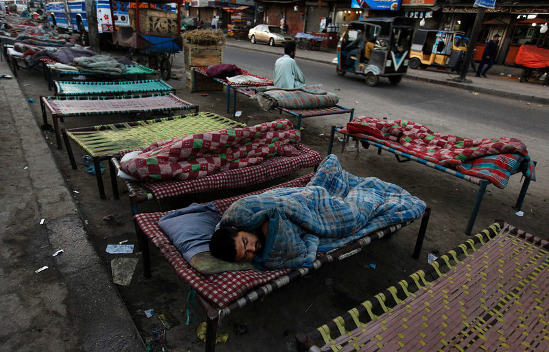 . A man sleeps on a charpoy bed along a road near a railway station in Karachi April 1, 2013. Charpoy bed guesthouses are only set up at night from 9pm to 7am for the homeless, passengers and drivers, charging about 40 Pakistani rupees ($0.40) per night. REUTERS/Akhtar Soomro