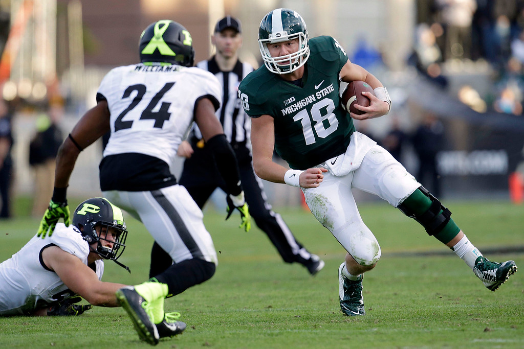 . Michigan State quarterback Connor Cook (18) looks to slide in front of Purdue defensive back Frankie Williams (24) during the second half of an NCAA college football game in West Lafayette, Ind.,  Saturday, Oct. 11, 2014. Michigan State won 45-31. (AP Photo/AJ Mast)