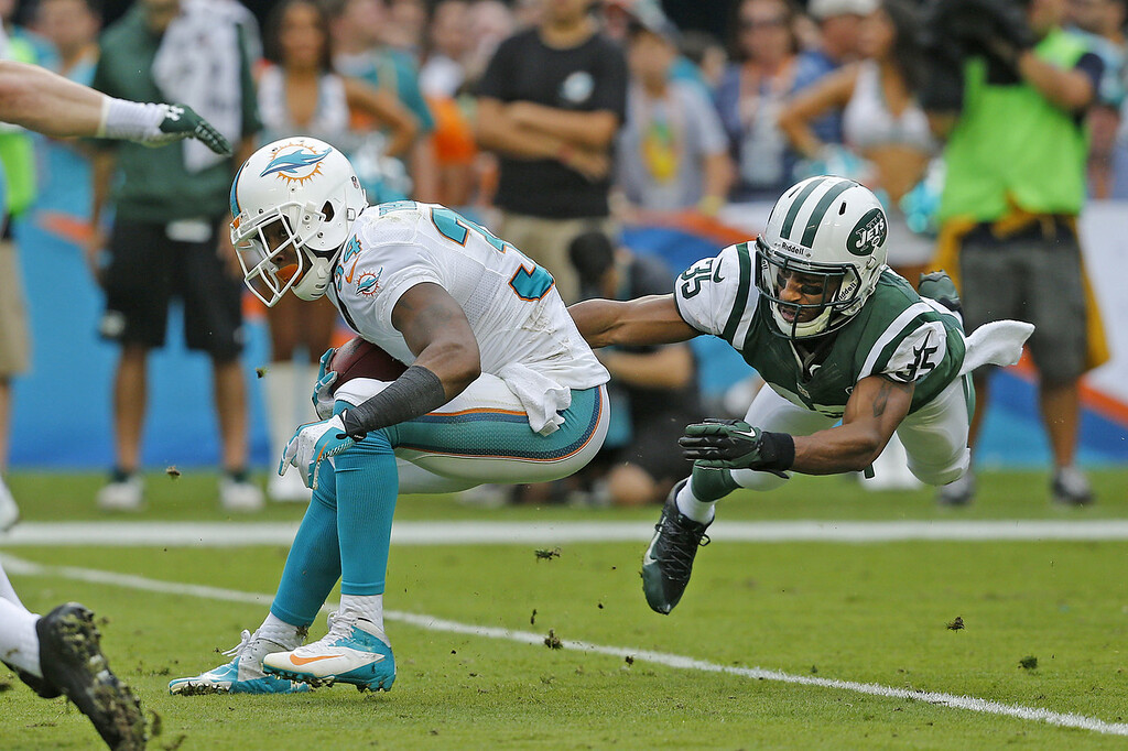 . Isaiah Trufant #35 of the New York Jets tackles Marcus Thigpen #34 of the Miami Dolphins as he runs with the ball on December 29, 2013 at Sun Life Stadium in Miami Gardens, Florida. (Photo by Joel Auerbach/Getty Images)