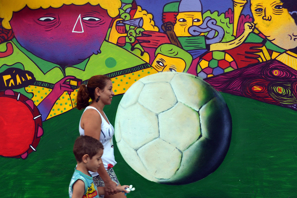 . A woman and a boy walk in front of a mural painting in Rio de Janeiro, Brazil on June 9, 2014, just three days ahead of the FIFA World Cup 2014.  AFP PHOTO / GABRIEL BOUYS/AFP/Getty Images