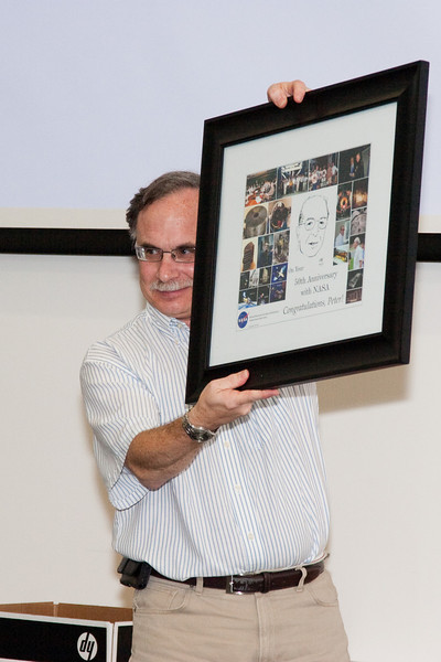 Rob Petre holds up the commemorative poster and asks people to sign its mat. -- Celebration of Peter Serlemitsos' 50 years at NASA/Goddard Space Flight Center (Sept 2011)