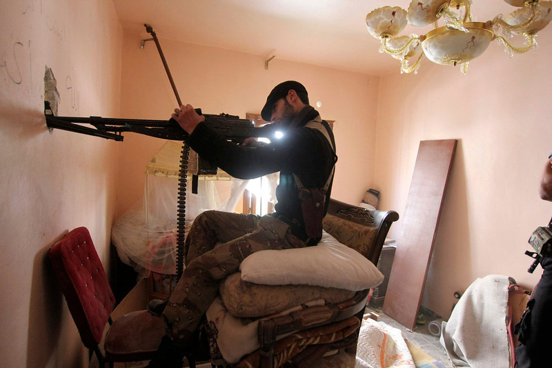. A Free Syrian Army fighter takes position inside a room as he points his weapon through a hole in Aleppo\'s Saif al-Dawla district March 20, 2013. REUTERS/Giath Taha