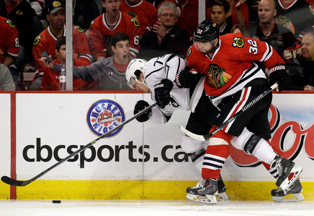. Los Angeles Kings\' Tyler Toffoli (73), left, is checked by Chicago Blackhawks\' Michal Rozsival (32) during the third period of Game 1 of the Western Conference finals in the NHL hockey Stanley Cup playoffs in Chicago on Sunday, May 18, 2014. The Blackhawks won 3-1. (AP Photo/Nam Y. Huh)