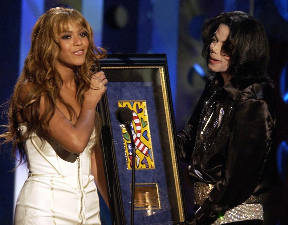 . Beyonce Knowles, left, presents Michael Jackson with a humanitarian award  during the Radio Music Awards Monday, Oct. 27, 2003 at the Aladdin Hotel in Las Vegas. (AP Photo/Joe Cavaretta)