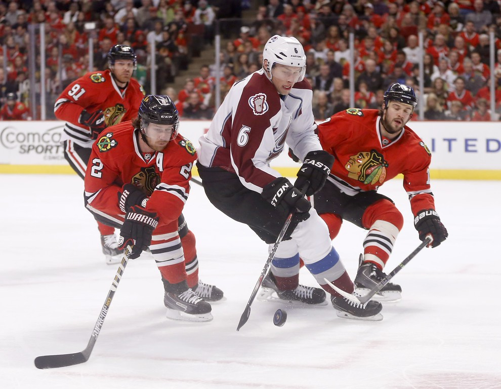 . Colorado Avalanche defenseman Erik Johnson (6) advances the puck between Chicago Blackhawks defenseman Duncan Keith (2) and Brent Seabrook, as Brad Richards (91) watches, during the first period of an NHL hockey game Tuesday, Jan. 6, 2015, in Chicago. (AP Photo/Charles Rex Arbogast)