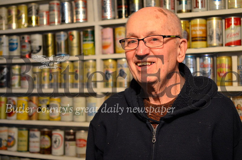 Rich Ordy, 82, of Butler stands with some of the 1,100 beer cans he keeps in his basement. Tanner Cole/Butler Eagle