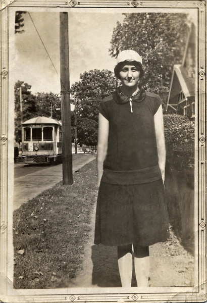 """Hazel Doss on a sidewalk with a street car in the background. On the back back of the photo is a rubber stamp from: """"Pettite Photo Co, 219 Commercial Street"""" (Springfield, Mo). If the photo doesn't look quite right it may be because it was badly damaged, and required extensive restoration."""