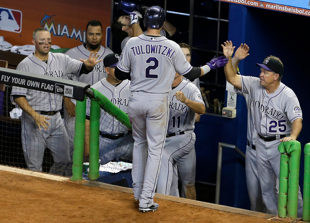 . Colorado Rockies\' Troy Tulowitzki (2) is greeted at the dugout by hitting coach Blake Doyle (25) and Michael Cuddyer, left, after scoring on a single by Nolan Arenado during the fifth inning of a baseball game against the Miami Marlins, Thursday, April 3, 2014, in Miami. (AP Photo/Lynne Sladky)