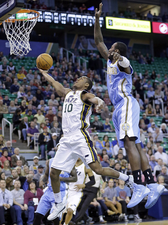 . Utah Jazz\'s Alec Burks (10) goes to the basket as Denver Nuggets\' J.J. Hickson (7) defends in the first quarter during an NBA basketball game Monday, Jan. 13, 2014, in Salt Lake City. (AP Photo/Rick Bowmer)