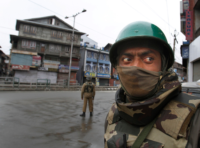 . An Indian paramilitary soldier stands guard on a road during a curfew in Srinagar, India, Friday, Jan. 15, 2013. Authorities have re-introduced a strict curfew across most of Indian-controlled Kashmir ahead of Friday prayers, as residents in the region simmer with anger over the secret execution of a Kashmiri man in the capital. (AP Photo/ Mukhtar Khan)