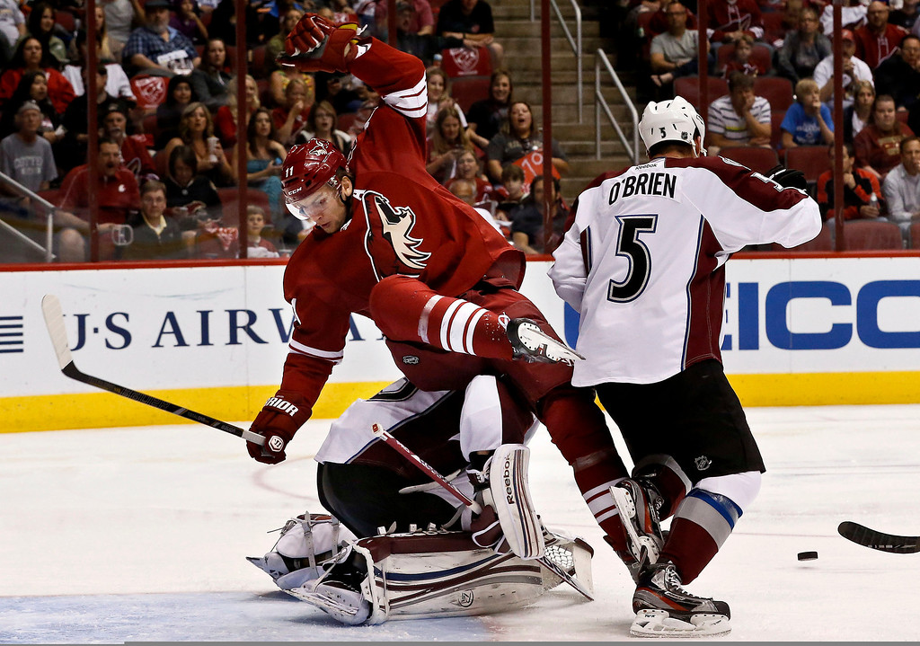. Phoenix Coyotes\' Martin Hanzal (11), of the Czech Republic, flips over Colorado Avalanche\'s Jean-Sebastien Giguere as the Avalanche\'s Shane O\'Brien (5) goes after the puck during the second period in an NHL hockey game, on Friday, April 26, 2013, in Glendale, Ariz. (AP Photo/Ross D. Franklin)