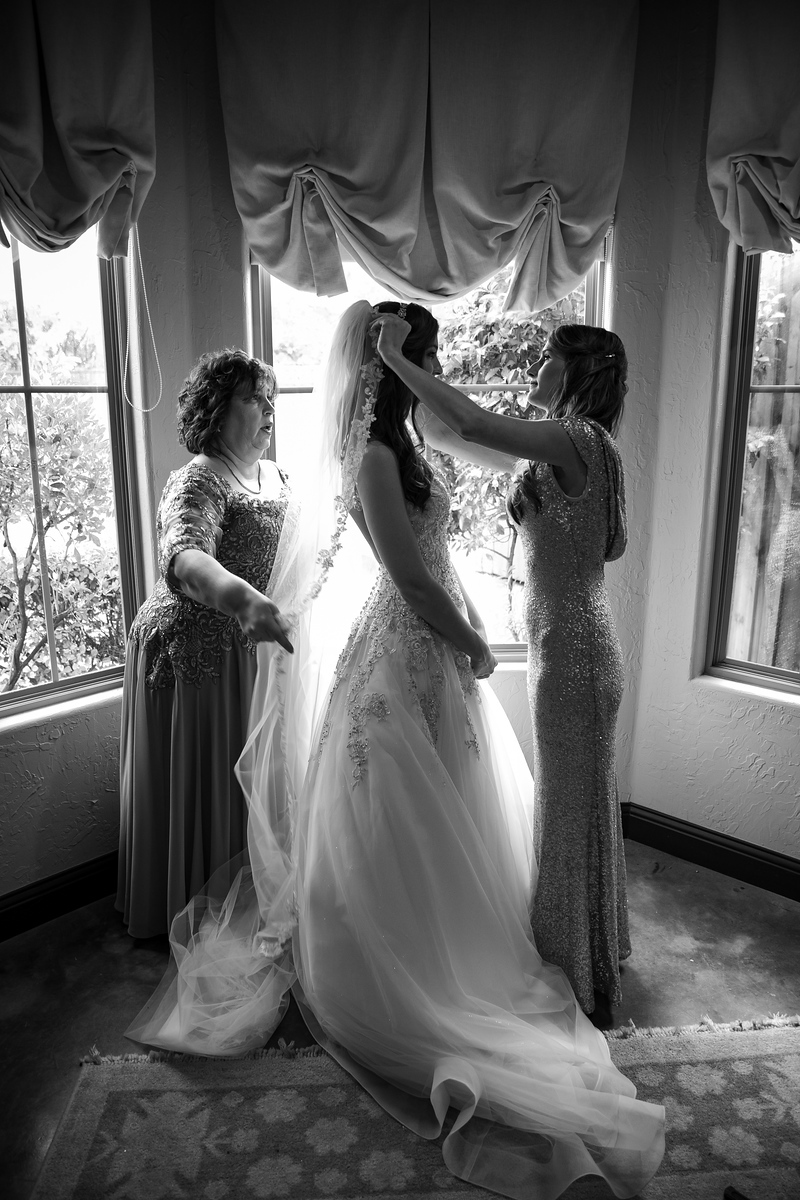black and white photo of a bride getting ready on her wedding day in front of three windows