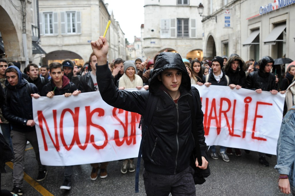 . Students hold pens and a banner reading \'We are Charlie\'\' in La Rochelle, on January 8, 2015, as they gathered to pay tribute to the twelve people killed the day before in an attack by two armed gunmen on the offices of French satirical newspaper Charlie Hebdo in Paris. A huge manhunt for two brothers suspected of massacring 12 people in an Islamist attack at a satirical French weekly zeroed in on a northern town Thursday after the discovery of one of the getaway cars.  As thousands of police tightened their net, the country marked a rare national day of mourning for Wednesday\'s bloodbath at Charlie Hebdo magazine in Paris, the worst terrorist attack in France for half a century. AFP PHOTO / XAVIER LEOTY/AFP/Getty Images