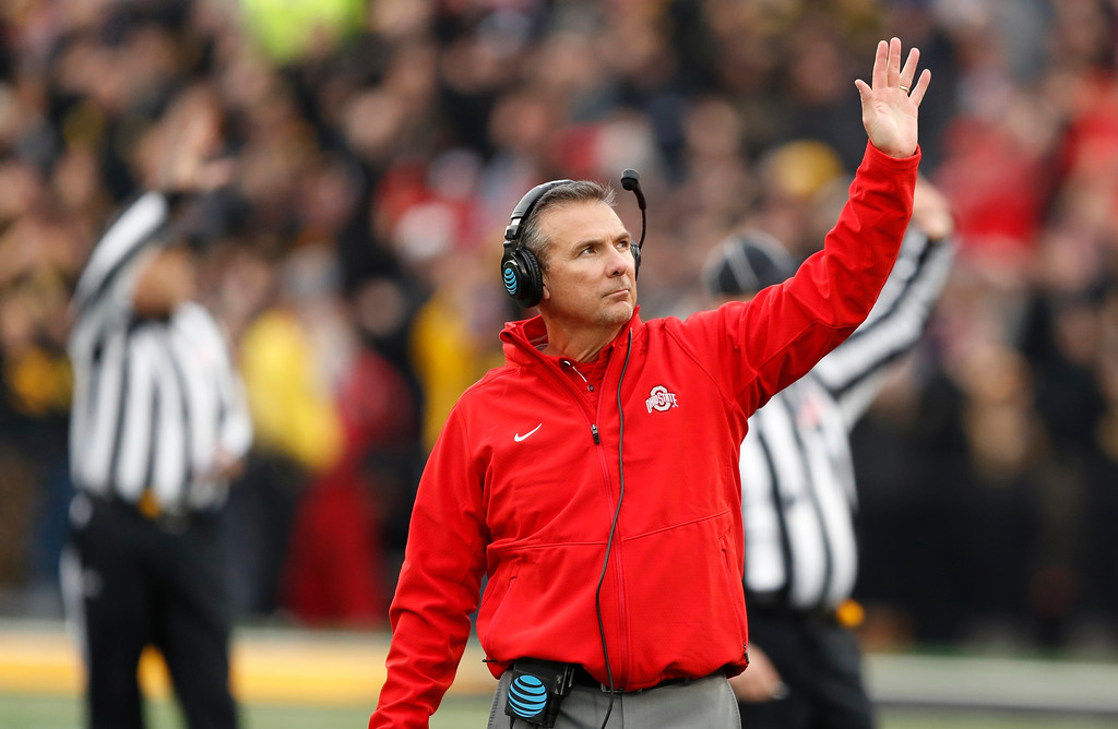 . In this Nov. 4, 2017, photo, Ohio State head coach Urban Meyer waves to children in the University of Iowa\'s children\'s hospital at the end of the first quarter of an NCAA college football game against Iowa in Iowa City, Iowa. In the new tradition, known as The Wave, at the end of the first quarter fans and players in the 70,585-seat Kinnick Stadium turn to wave to the pediatric patients watching from the hospital, a 12-story building that overlooks the stadium from across the street. (AP Photo/Charlie Neibergall)