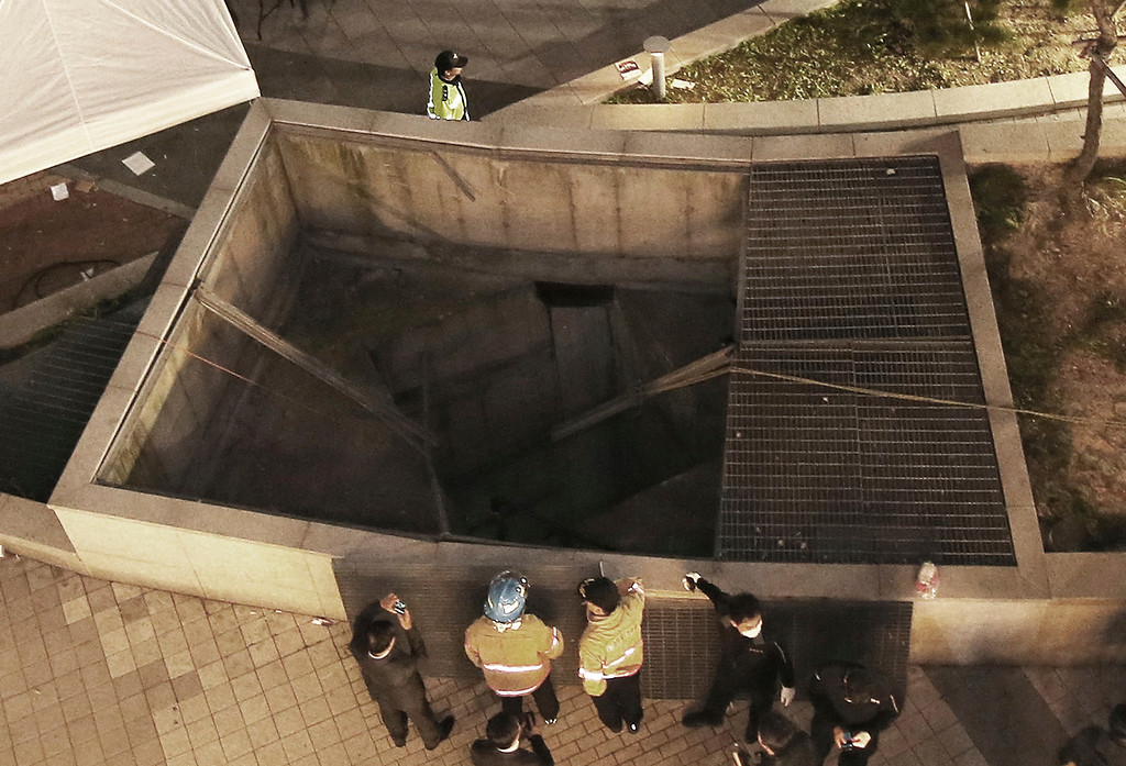 . Rescue workers stand around a collapsed ventilation grate at an outdoor theater in Seongnam, south of Seoul, South Korea, Friday, Oct. 17, 2014. (AP Photo/Yonhap, Shin Young-geun)