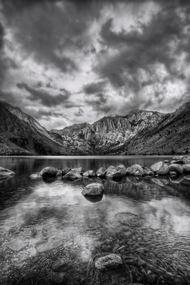 <h2>Convict Lake</h2> My first visit there. I love that feeling of the first time... your heart quickens, your eyes get all sharp and darty at the new sights, even my stomach jumps around a little at the excitement of NEW.   I'm big on the story too - and I love hearing them about the places I visit. Convict Lake was named after an incident in 1871, where a group 'o thugs, er, 'convicts' escaped from prison in Carson City. That's 200 miles away. So a buncha lawmen, er, a 'posse' chased those buggers all the way down here, where they had a shootout. The sheriff was killed, as was his Indian guide. They named the lake after the convicts, the mountain (Mt. Morrison) after the sheriff. Nobody named anything after the Indian guide, which strikes me as just pure ungrateful.   It was a moody, weathery day... kinda fitin' with the story that goes with it. But I just went with the vibe and took this picture to share with y'all.