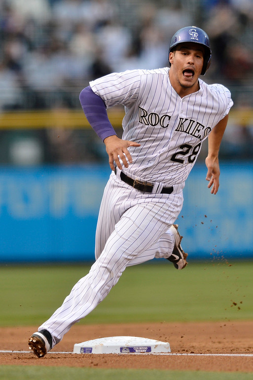 . Colorado Rockies\' Nolan Arenado rounds third base in route to score on an RBI double hit by Justin Morneau against the New York Mets during the first inning of a baseball game, Friday, May 2, 2014, in Denver. (AP Photo/Jack Dempsey)