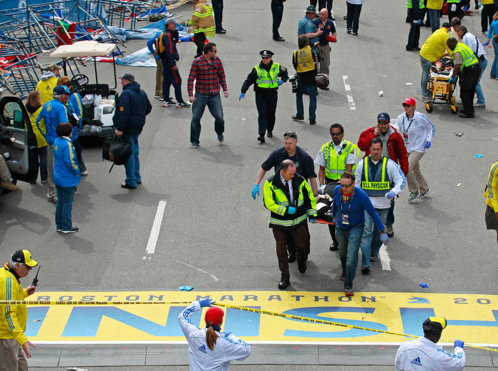. Medical workers wheel the injured across the finish line during the 2013 Boston Marathon following an explosion in Boston, Monday, April 15, 2013. Two explosions shattered the euphoria of the Boston Marathon finish line on Monday, sending authorities out on the course to carry off the injured while the stragglers were rerouted away from the smoking site of the blasts. (AP Photo/Charles Krupa)