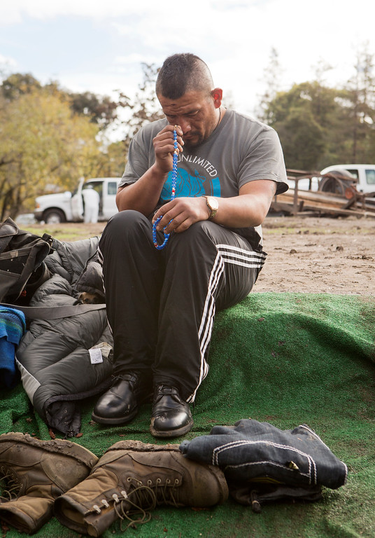 . As construction crews clear campsites behind him, Valentin Cortez-Oseguer prays before he leaves the homeless encampment known as The Jungle in San Jose, Calif., on Thursday, Dec. 4, 2014. (LiPo Ching/Bay Area News Group)