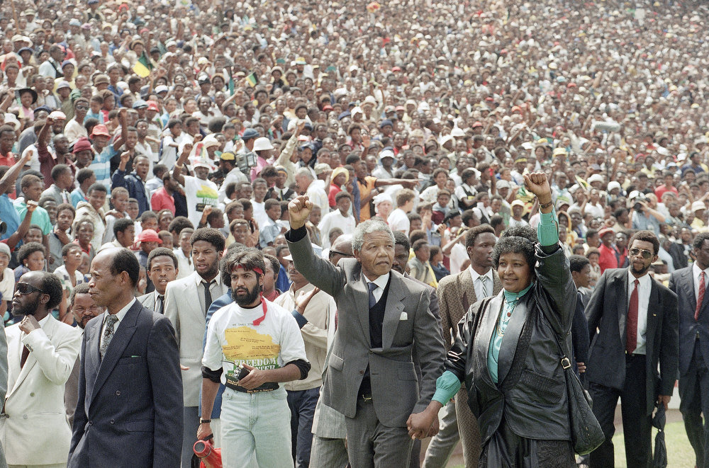 Description of . Nelson Mandela and Winnie Mandela give back power salutes as they enter Soweto's Soccer City stadium, South Africa Tuesday, Feb. 13, 1990. 120,000 thousand people packed the venue to hear his speech. (AP Photo/Udo Weitz)