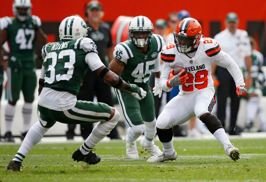 . Cleveland Browns running back Duke Johnson (29) avoids the tackle by New York Jets strong safety Jamal Adams (33) and free safety Rontez Miles (45) during the first half of an NFL football game, Sunday, Oct. 8, 2017, in Cleveland. (AP Photo/Ron Schwane)