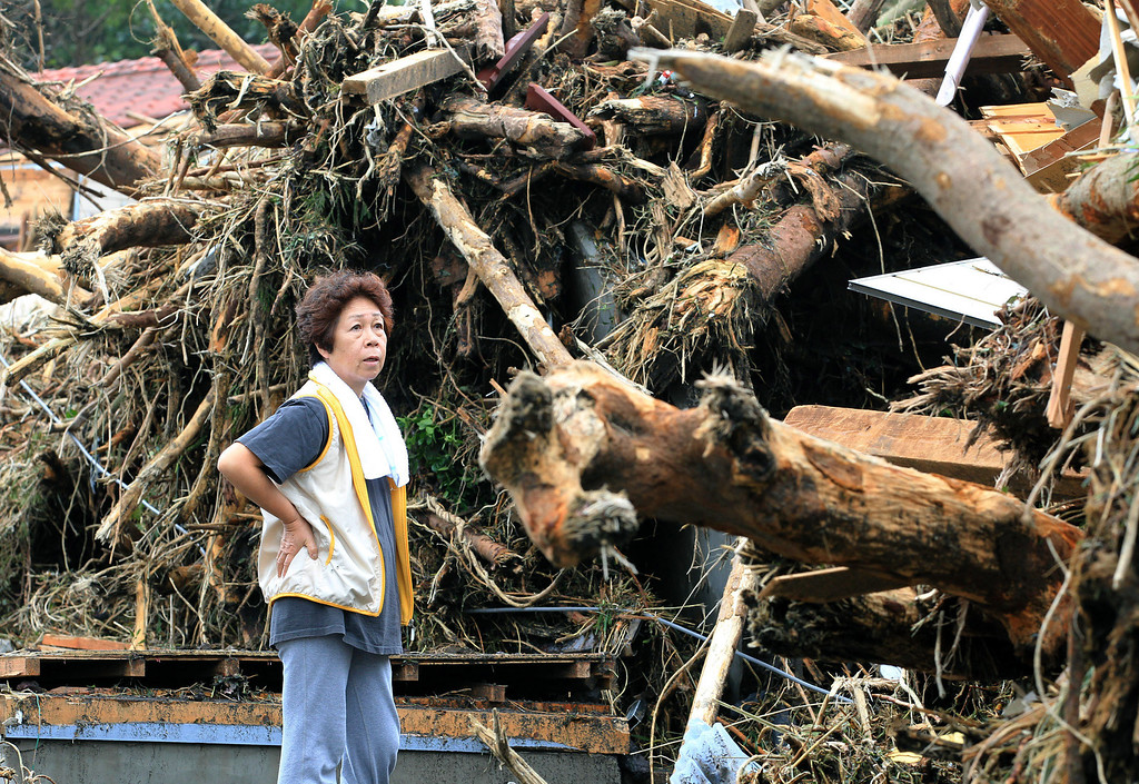 . A woman looks at the aftermath of landslides in the rubble of smashed houses in Oshima after a powerful typhoon hit Izu Oshima island, about 120 kilometers (75 miles) south of Tokyo Wednesday morning, Oct. 16, 2013. (AP Photo/Kyodo News)