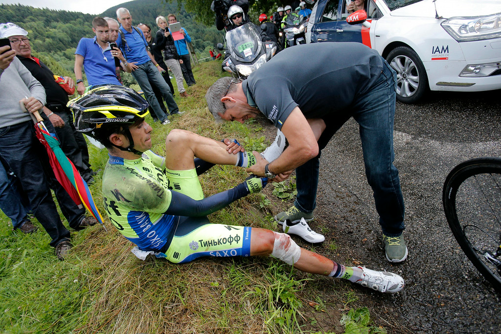 . A team member helps Spain\'s Alberto Contador change race shoes after he crashed during the tenth stage of the Tour de France cycling race over 161.5 kilometers (100.4 miles) with start in Mulhouse and finish in La Planche des Belles Filles, France, Monday, July 14, 2014. Contador withdrew from the race as a result of the crash. (AP Photo/Christophe Ena)