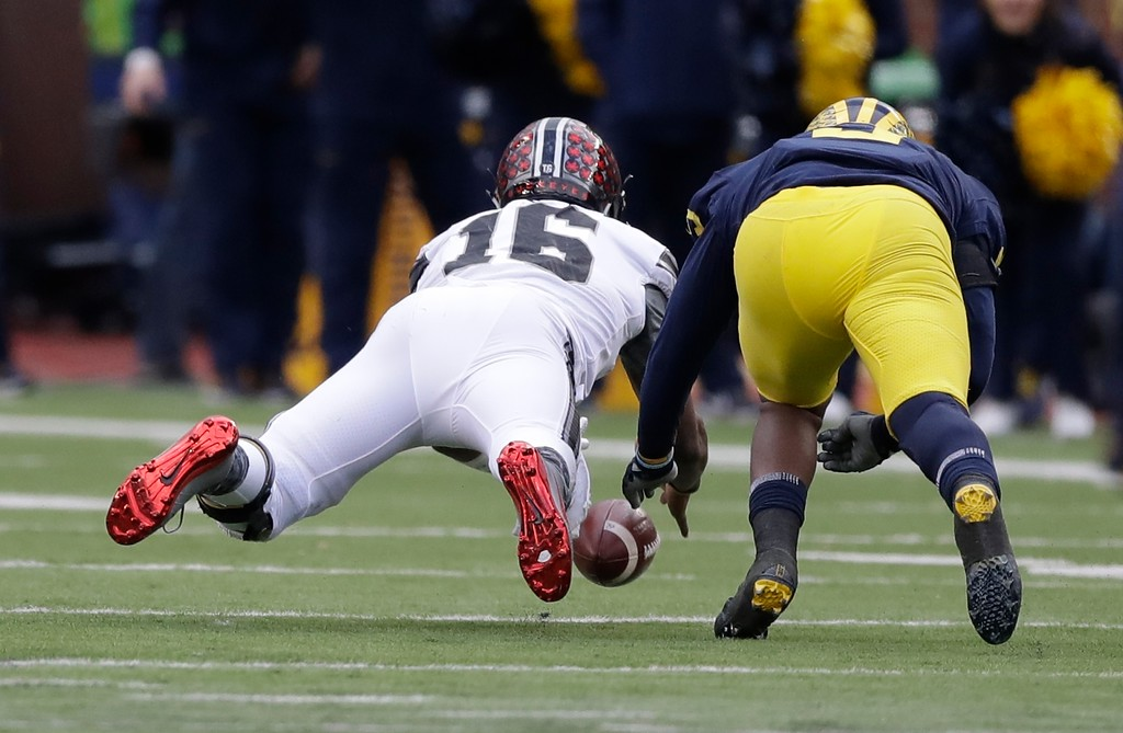 . Ohio State quarterback J.T. Barrett (16) and Michigan linebacker Mike McCray chase Barrett\'s fumble that was recovered by Barrett during the first half of an NCAA college football game, Saturday, Nov. 25, 2017, in Ann Arbor, Mich. (AP Photo/Carlos Osorio)