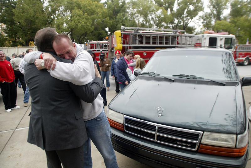 Jesse Hunt (right) gives an emotional hug to Executive Director of The Well Ministry of Rescue, Scott Bertolini (left), after Hunt was surprised by a the gift of a van for his family for the Toy Drive by the Chico Fire Dept. Saturday - halley photo 12/17/05
