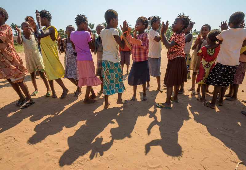 """Misc. photos at Nganza Child Friendly space, which Kapinga Alphoncine, 13 yr-old girl (white dress, white beads in her hair) attends.  Kapinza lives with her widowed grandmother, Kapinga Godelive, 66 and her 3 brothers: 1-Francois Ngondo, 14 2-Mbuyamba Phillip, 9 3-Beya Honore, 6 Kananga, DRC Democratic Republic of Congo.  CFS Kapinga also love the Nganza Child Friendly Space (CFS.) There she plays games, soccer and dances but also learns things like how to mend her clothes. """"The CFS is a good place. I've learned to mend my clothes. And I like to play soccer.""""  In the afternoon there, Kapinga and 3 friends play a dice game called Game of Six. There are about 1,985 children who attend this CFS, in two sessions. In addition to games, the """"animators,"""" volunteers who supervise the children, also teach the children about children's rights, health and skills like mending their clothes.  The biggest challenge at World Vision's CFS' is providing psycho-social care for former child soldiers.  We have an interview with Chief Animator, Jean Nicolas Kankonde, 53. Kankonde says there are two kinds of former militia chidren. """"There are two kinds of children. (Some) easily accept it and learn to become collaborative. But some think that if they admit being in a militia, they will be turned into the government."""" Here, only 15 of the 1900+ children have admitted to being in militias. 11 boys and 4 girls.  The Chief Animator says to make true progress here, children need to study, elementary education needs to be free and teachers need to be paid well.  Inside Kapinga's four-room house the walls are paint splattered. There is little furniture except for two small tables and an old cabinet. On top sits a dusty old television. A peek behind reveals that it has no cord. Kapinga sits on a low, wooden bench against one wall reading an old school exercise book of English lessons. """"Good morning my friends, good morning.""""  Her English is good in spite of a mispronunciation here and there. Hi"""