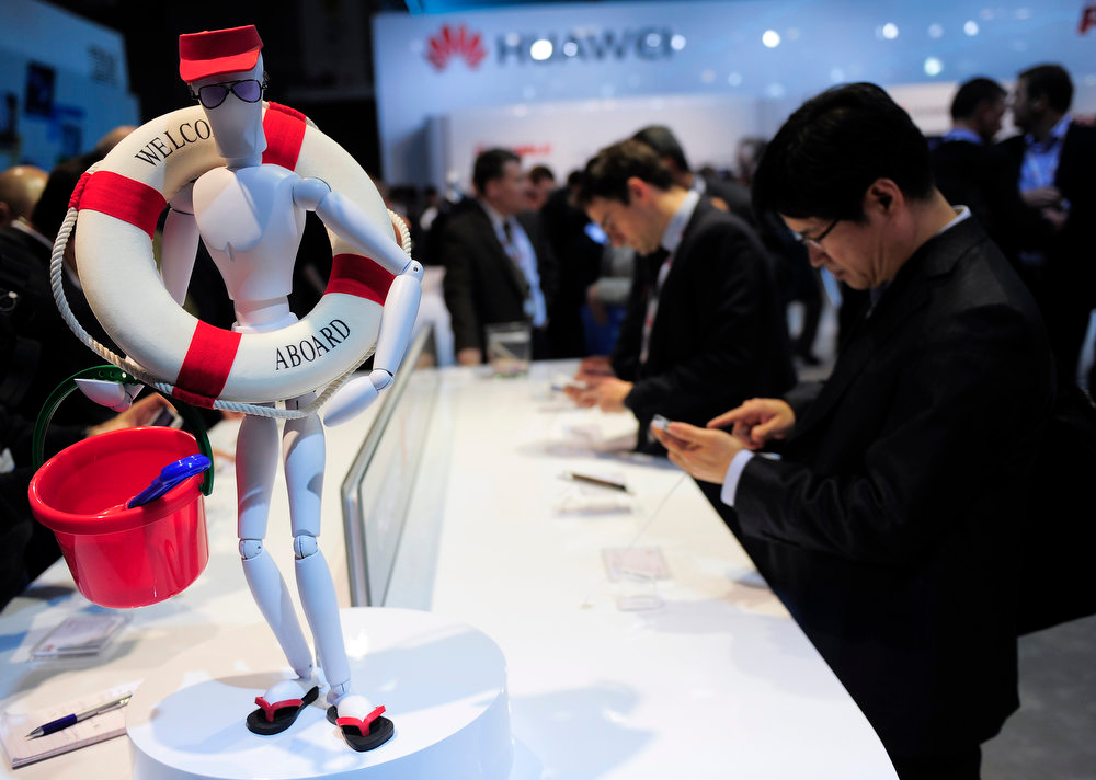 . Visitors check smartphones at a Huawei stand in Barcelona on February 26, 2013, on the second day of the 2013 Mobile World Congress . The 2013 Mobile World Congress, the world\'s biggest mobile fair, is held from February 25 to 28 in Barcelona. JOSEP LAGO/AFP/Getty Images
