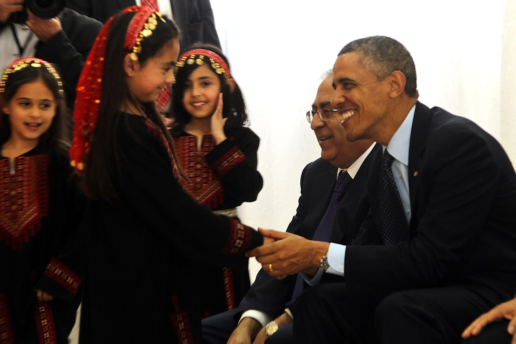 . U.S. President Barack Obama (R) is welcomed by Palestinian girls during his visit to Al Bera Youth Center March 21, 2013 in Ramallah, the West Bank.   (Photo by Alaa Badarneh-Pool/Getty Images)