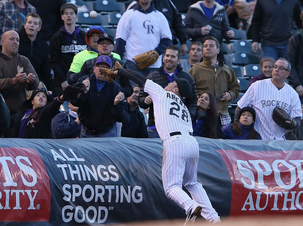 . Third baseman Nolan Arenado #28 of the Colorado Rockies leans over the tarp to catch a pop foul by Curtis Granderson #3 of the New York Mets in the second inning at Coors Field on May 1, 2014 in Denver, Colorado.  (Photo by Doug Pensinger/Getty Images)