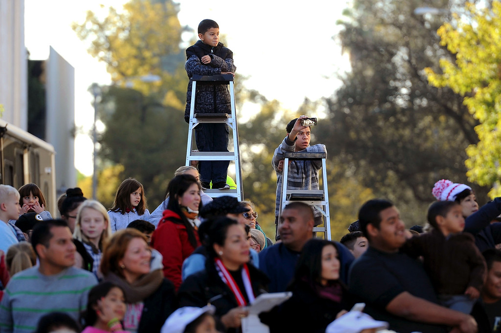 . Youngsters use ladders to watch the 2014 Rose Parade in Pasadena, CA January 1, 2014.(Andy Holzman/Los Angeles Daily News)