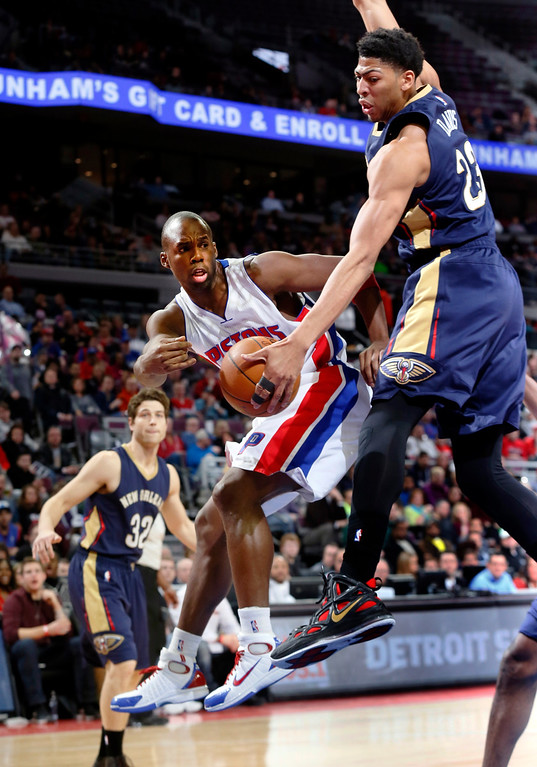 . Detroit Pistons guard Jodie Meeks (20) passes around New Orleans Pelicans forward Anthony Davis (23) during the first half of an NBA basketball game in Auburn Hills, Mich., Wednesday, Jan. 14, 2015. (AP Photo/Paul Sancya)