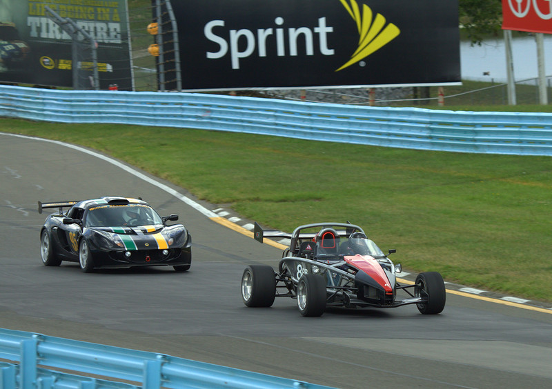 """Ariel Atom 2 leading a Lotus Exige Cup Car, coming up through the """"Esses"""" at Watkins Glen International"""