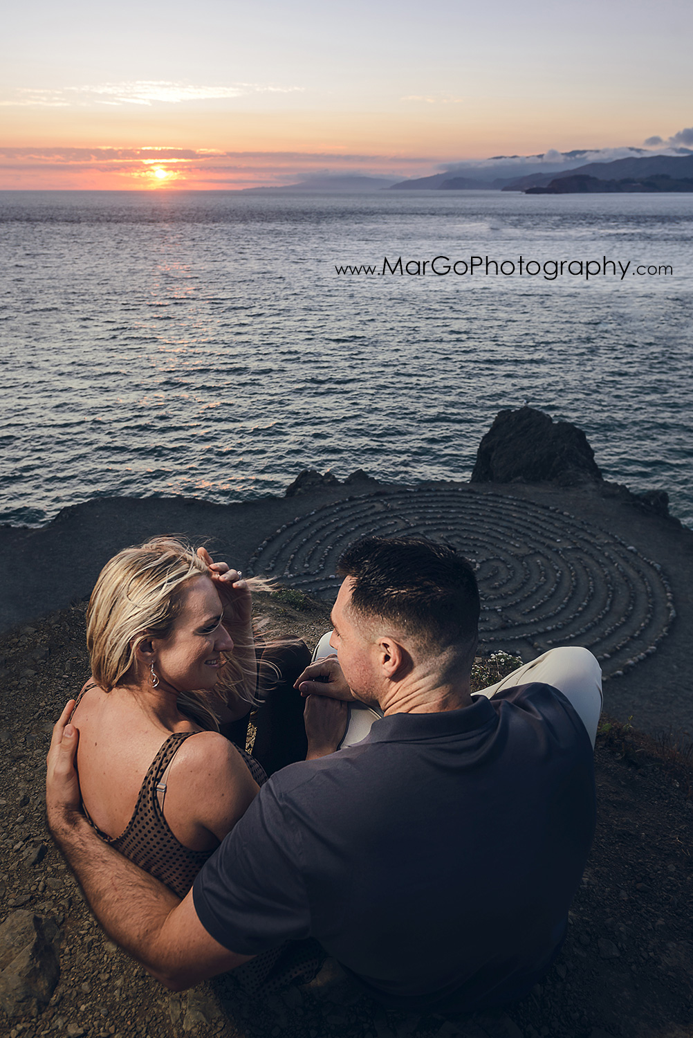 man in navy blue shirt and woman in brown tunic looking at each other sitting above the stone labyrinth during sunset engagement session at San Francisco Lands End