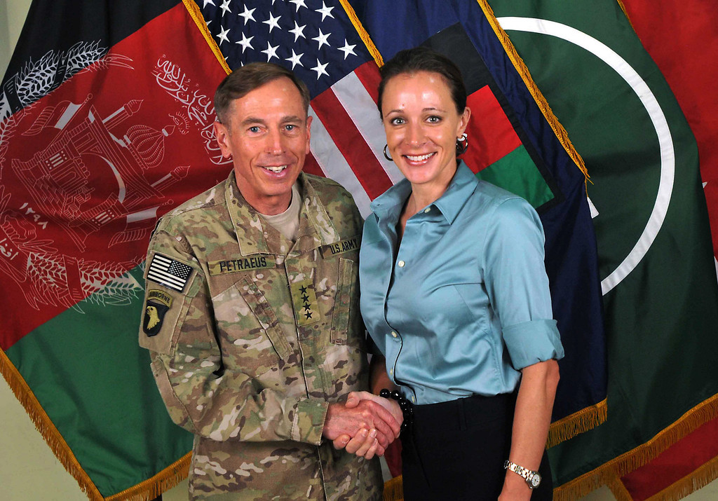 ". This July 13, 2011 file photo, made available on the International Security Assistance Force\'s Flickr website shows the former Commander of International Security Assistance Force and U.S. Forces-Afghanistan Gen. Davis Petraeus, left, shaking hands with Paula Broadwell, co-author of  ""All In: The Education of General David Petraeus.\"" Petraeus resigned as CIA director over his extramarital affair with his biographer, Broadwell. (AP Photo/ISAF, File)"