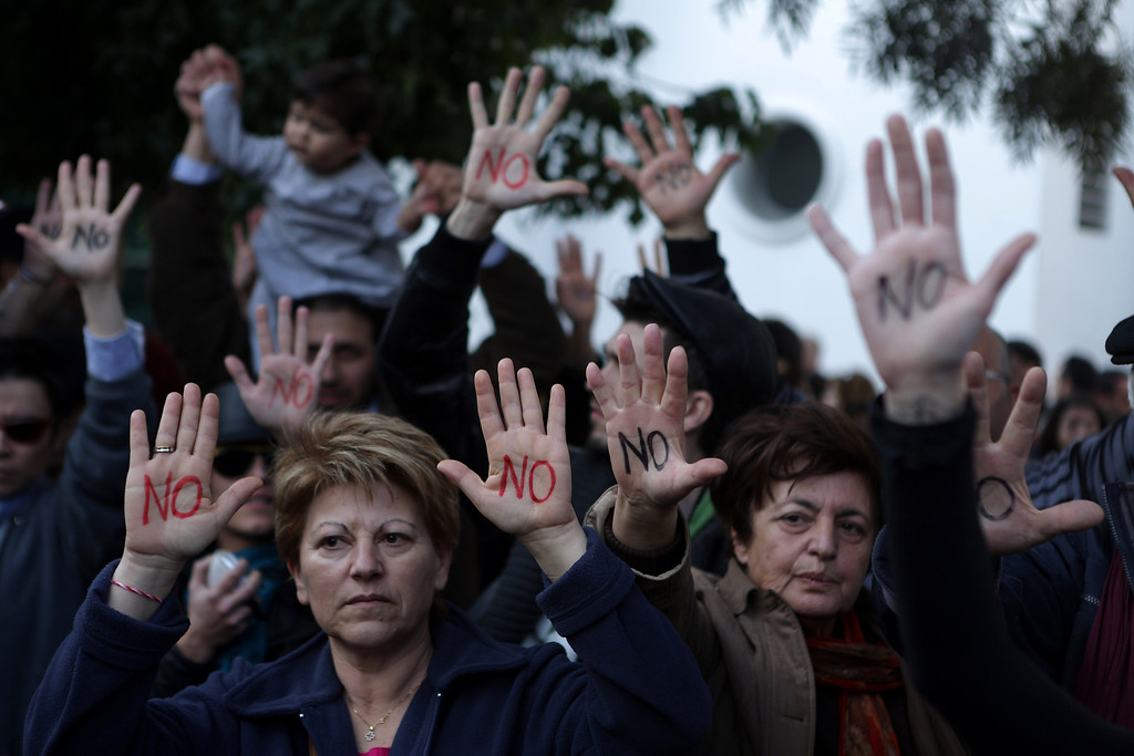 ". Cypriots show their palms reading ""No\"" during a protest against an EU bailout deal outside the parliament in Nicosia on March 18, 2013.  PATRICK BAZ/AFP/Getty Images"