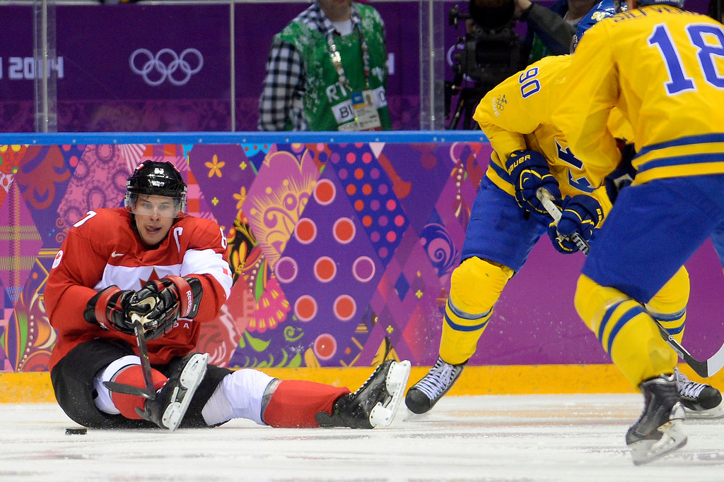. Sidney Crosby (87) of Canada controls the puck against Sweden from a seated position during the second period of the men\'s ice hockey gold medal game. Sochi 2014 Winter Olympics on Sunday, February 23, 2014 at Bolshoy Ice Arena. (Photo by AAron Ontiveroz/ The Denver Post)